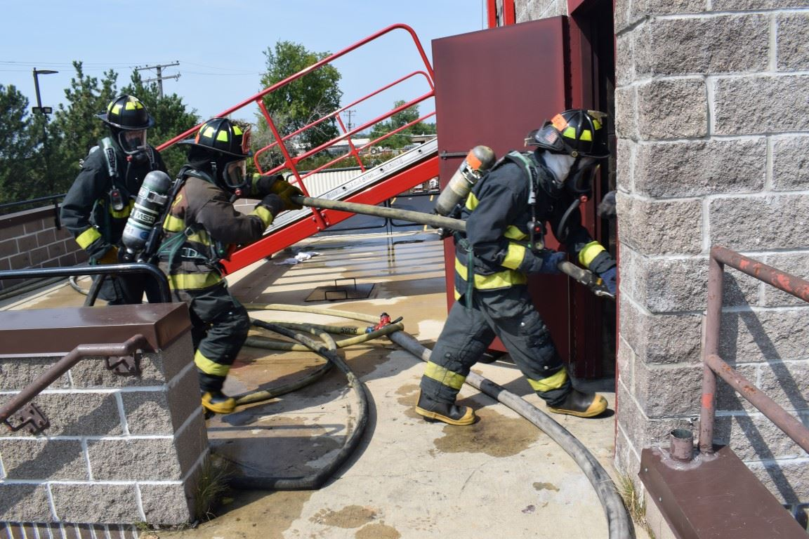 Three firemen in gear entering building